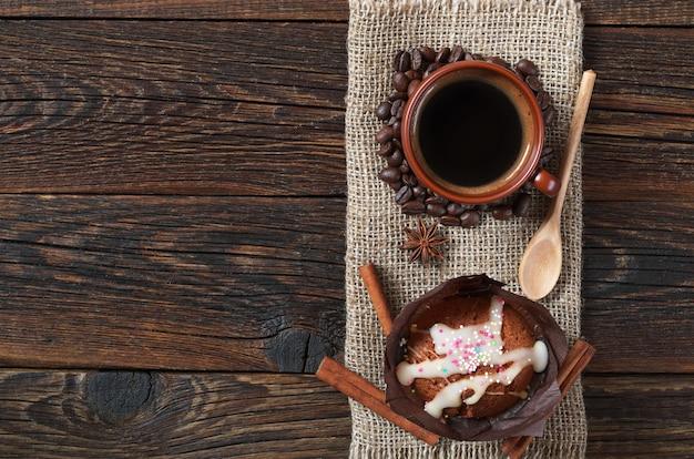 Kopje warme koffie en muffin in pakpapier op donkere houten, bovenaanzicht