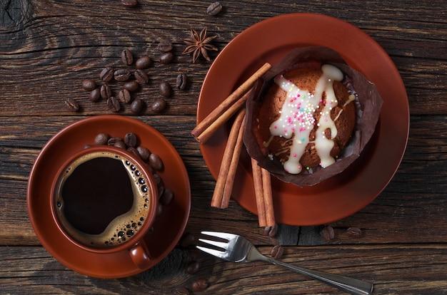 Kopje warme koffie en muffin in pakpapier op donkere houten tafel, bovenaanzicht