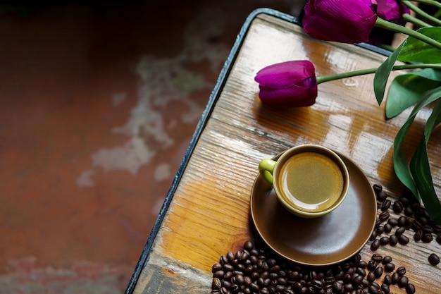Kopje warme koffie espresso met koffiebonen en stof tulp bloemen. Premium Foto