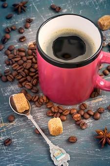 Kopje warme koffie met schuim op de achtergrond van koffiebonen.