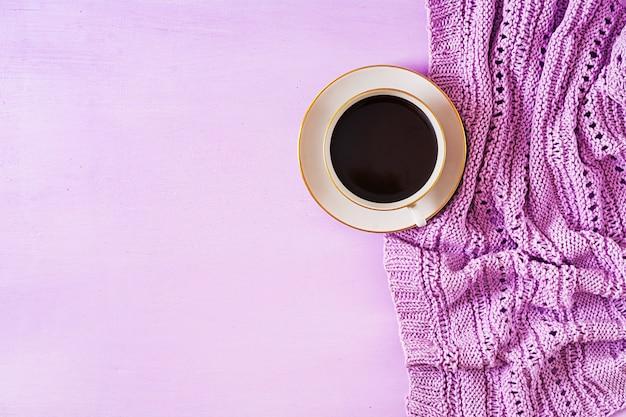 Kopje warme koffie op violet tafel, close-up foto gebreide trui met mok