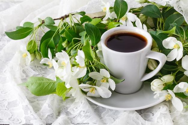 Kopje warme lekkere koffie in zeer lente bloemen omgeving.