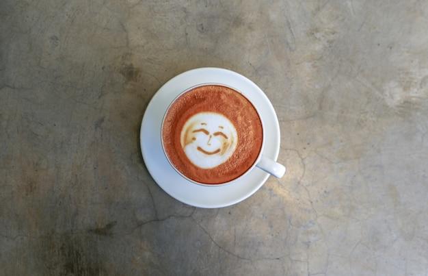 Kopje warme smakelijke cappucino met een glimlach als kunst latt onn betonnen achtergrond