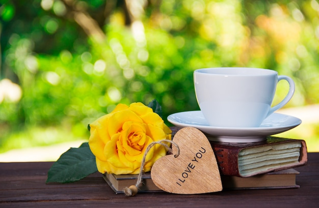 Kopje zomer thee op stapel boeken en geurige gele roos