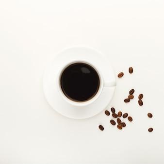 Kopje zwarte koffie en geroosterde bonen op witte geïsoleerde achtergrond. bovenaanzicht op verkwikkende drank. mockup voor advertentieontwerp, kopieer ruimte