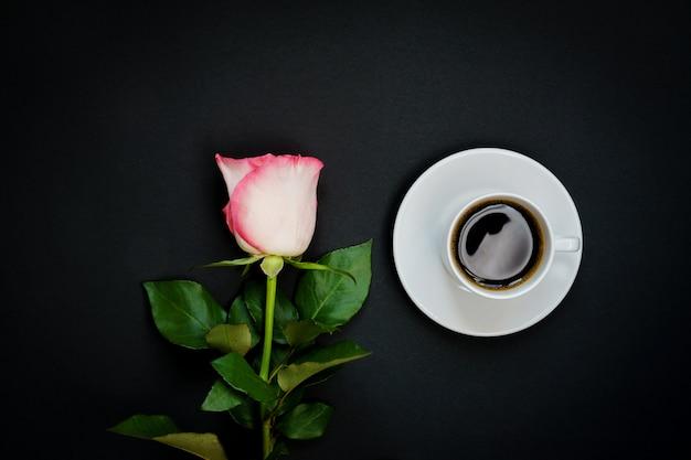 Kopje zwarte koffie en roze roos op zwart, bovenaanzicht, kopie ruimte.
