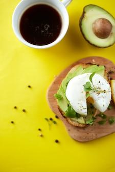 Kopje zwarte koffie en sandwich met avocado en gepocheerd ei, zaden en microgreen geel oppervlak kopieer ruimte gezond ontbijt