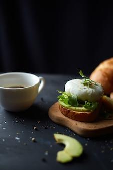 Kopje zwarte koffie en sandwich met avocado en gepocheerd ei, zaden en microgreen zwarte oppervlakte kopieer ruimte gezond ontbijt