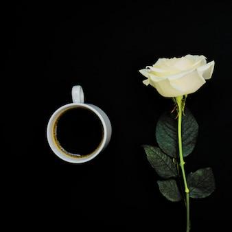 Kopje zwarte koffie en witte roos op zwart, bovenaanzicht, kopie ruimte. afgezwakt beeld