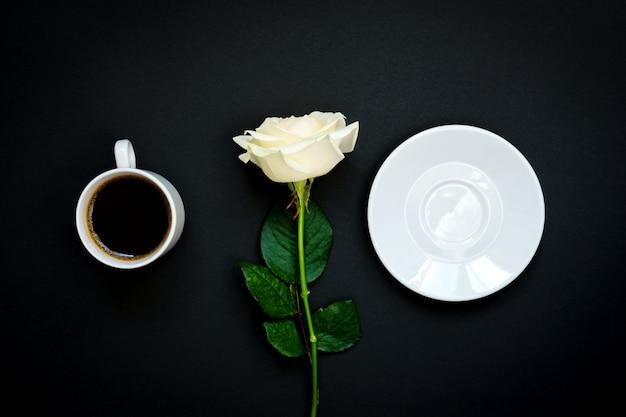 Kopje zwarte koffie en witte roos op zwart, bovenaanzicht, kopie ruimte.