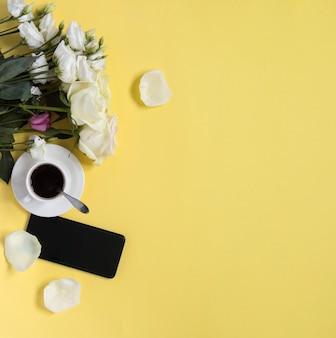 Kopje zwarte koffie met bloemen en smartphone op gele achtergrond met kopieerruimte