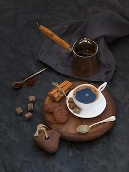 Kopje zwarte koffie met chocoladekoekjes, kaneelstokjes en rietsuikerklontjes op rustieke houten bord over donkere steen.