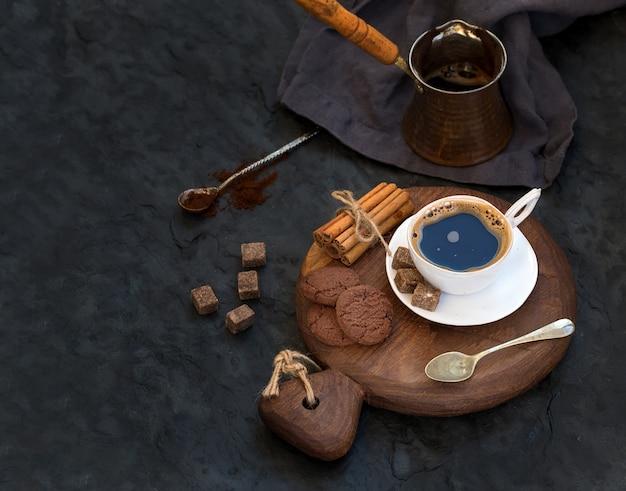 Kopje zwarte koffie met chocoladekoekjes, kaneelstokjes en rietsuikerklontjes op rustieke houten bord over donkere stenen achtergrond.