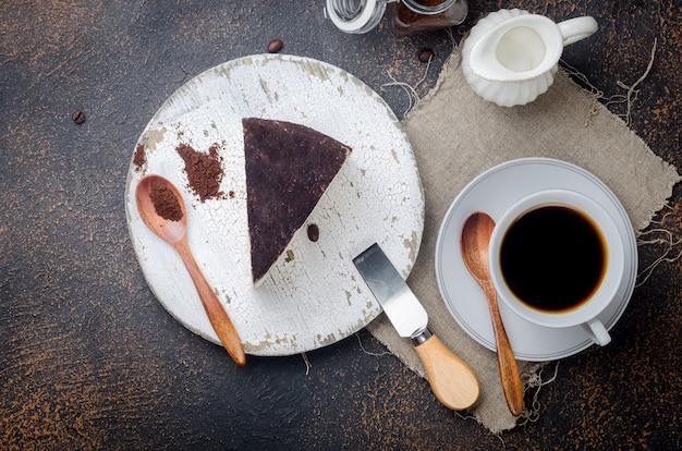 Kopje zwarte koffie met een stuk zachte kaas in gemalen koffie