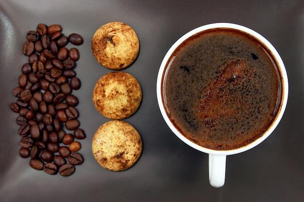 Kopje zwarte koffie met koekjes en bonen op een donkere plaat. hete drankjes