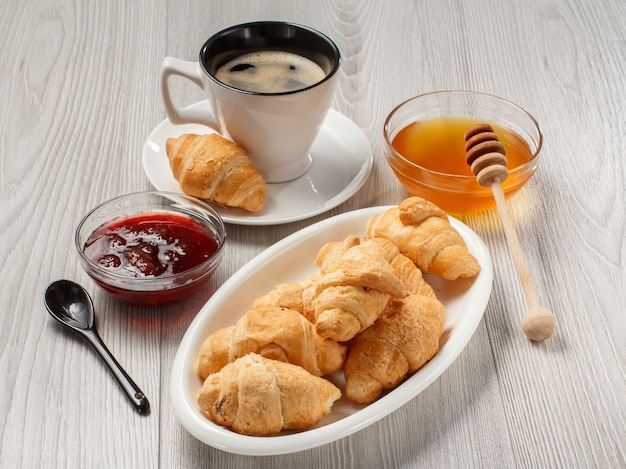 Kopje zwarte koffie met schotel, verse croissants op witte porseleinen schotel, honing en aardbeienjam in glazen kommen met grijze houten achtergrond