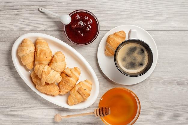Kopje zwarte koffie met schotel, verse croissants op witte porseleinen schotel, honing en aardbeienjam in kommen met grijze houten achtergrond