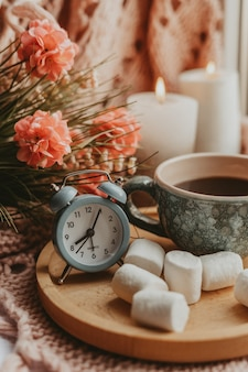 Kopje zwarte koffie op een houten dienblad met dessert en boeket in kleur en met kaarsen