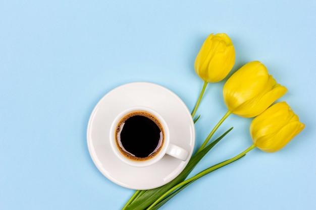 Kopje zwarte koffie op een schotel en een boeket gele tulpen bloemen op een blauwe achtergrond bovenaanzicht