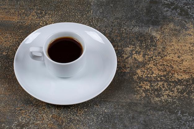 Kopje zwarte koffie op marmeren oppervlak.
