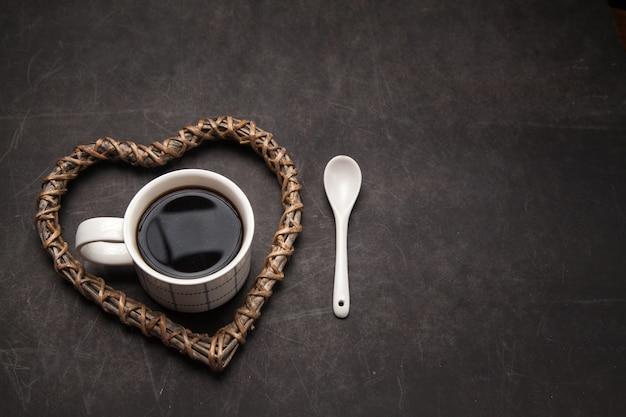 Kopje zwarte koffie voor koffieliefhebbers americano in de mok op donkere achtergrond met houten hart