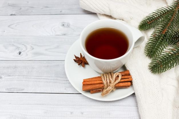 Kopje zwarte thee bedekt met sjaal. kerstboom op achtergrond. winter concept.