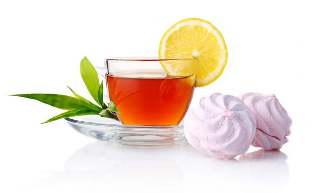 Kopje zwarte thee met citroen, groene bladeren en marshmallow geïsoleerd