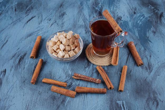 Kopje zwarte thee met kom bruine suiker op blauwe ondergrond.