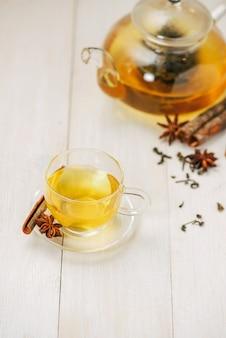 Kopje zwarte thee met kruiden op witte houten achtergrond.