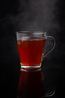 Kopje zwarte thee met stoom op een donkere achtergrond