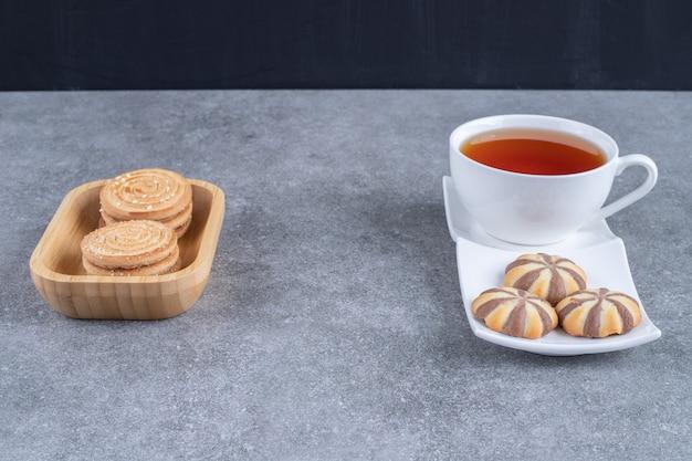 Kopje zwarte thee met verschillende koekjes op marmeren oppervlak