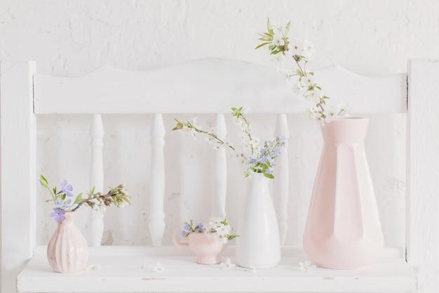 Kopjes en vazen met lentebloemen op vintage houten witte plank