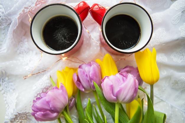 Kopjes koffie en boeket tulpen
