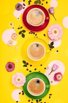Kopjes koffie en kleurrijke papieren cirkels op gele tafel