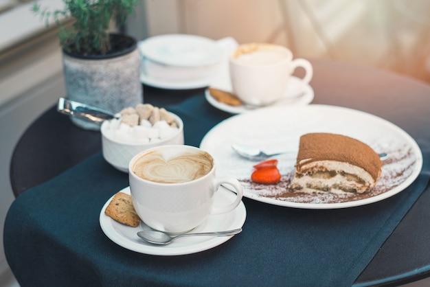 Kopjes koffie en tiramisu op zwarte tafel met prachtige latte art hartvormig.