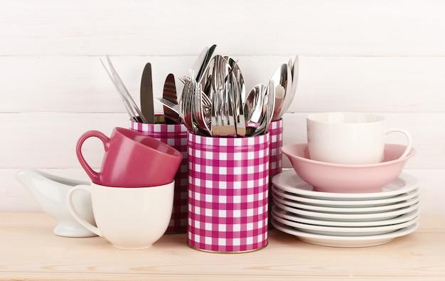 Kopjes, kommen en ander keukengerei in metalen containers geïsoleerd op een lichte ondergrond