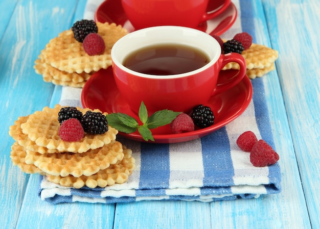 Kopjes thee met koekjes en bessen op tafel close-up