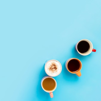 Kopjes warme dranken, koffie, cappuccino, koffie met melk op een blauwe ondergrond. concept coffeeshop, vrienden ontmoeten, ontbijt met vrienden, vriendelijk team. plein. plat lag, bovenaanzicht