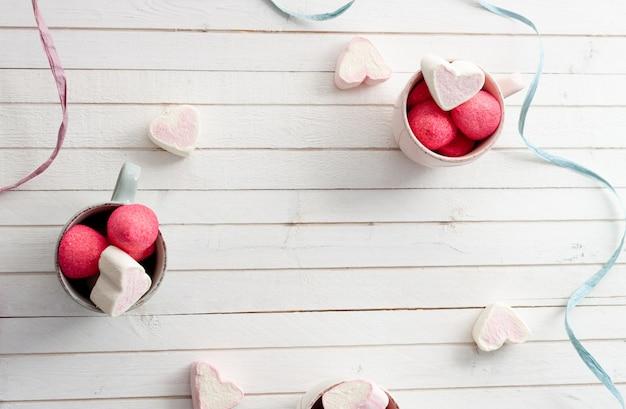 Kopjes zoete en hartvormige marshmallows