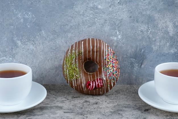 Kopjes zwarte thee met chocolade berijpte doughnut op marmer.