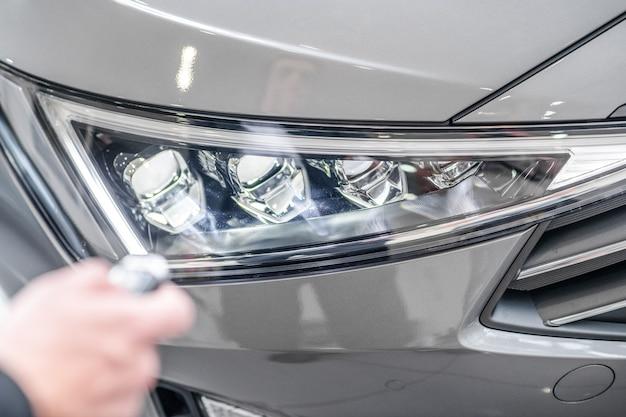 Koplamp. glanzende koplamp van auto en hand met sleutelhanger in de buurt, geen gezicht zichtbaar