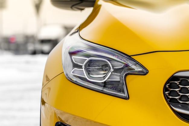 Koplamp lamp van nieuwe auto's close-up detail op een van de led-koplampen moderne gele auto exterieur