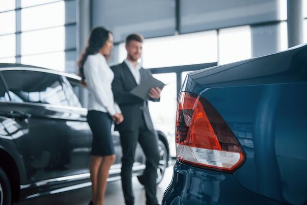 Koplampen achter. vrouwelijke klant en moderne stijlvolle bebaarde zakenman in de auto-salon