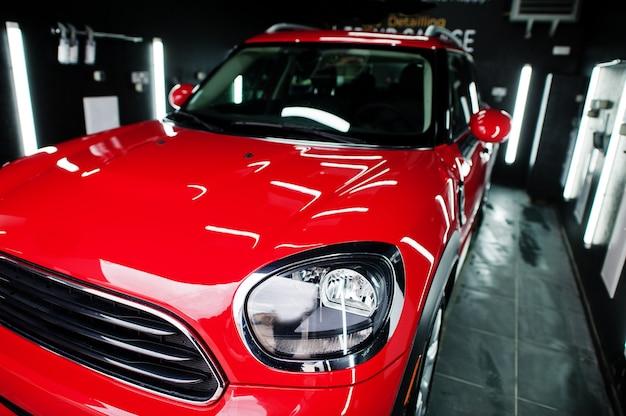 Koplampen en motorkap van sport rode auto in garage
