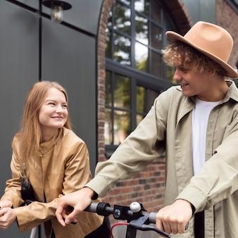 Koppel buiten in de stad met elektrische scooters