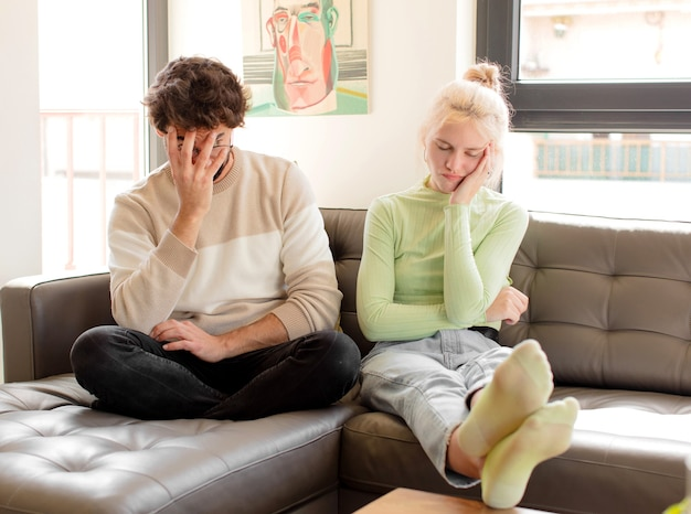 Koppel dat zich verveeld, gefrustreerd en slaperig voelt na een vermoeiende, saaie en vervelende taak, waarbij het gezicht met de hand wordt vastgehouden