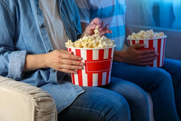Koppel film kijken op de bank en eet popcorn. eten om films te kijken