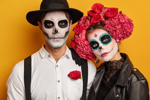 Koppel heeft gezichten geschilderd, neemt deel aan zombiewandeling, herdenkt doden tijdens dag des doods in mexico, draagt make-up voor halloweenfeestjes