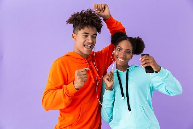 Koppel in kleurrijke kleding dansen terwijl u luistert naar muziek samen met koptelefoon, geïsoleerd over violet muur