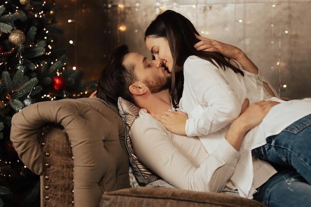Koppel in witte shirts knuffelen en willen kussen op de beige bank bij de kerstboom.